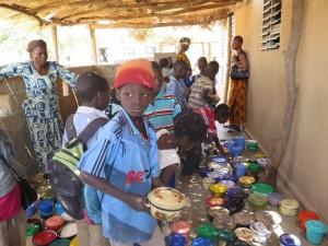 Les enfants de l'école de Pog Nini (secteur 5), viennent chercher les uns après les autres leur plat rempli ce jour de riz aux haricots.