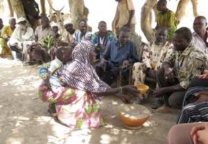 """Une femme du village présente au chef du quartier la calebasse contenant """"l'eau de bienvenue"""" qui va circuler"""